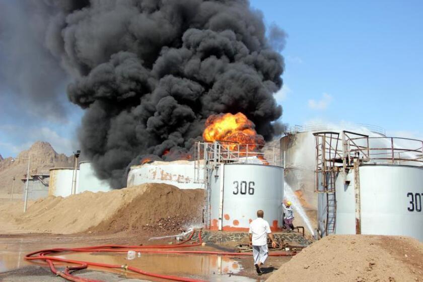 Los bomberos trabajan para extinguir un incendio en un tanque de almacenamiento de petróleo en la refinería de petróleo principal en la ciudad portuaria meridional de Adén, Yemen, el 12 de enero de 2019. EFE/EPA/NAJEEB ALMAHBOOBI/Archivo