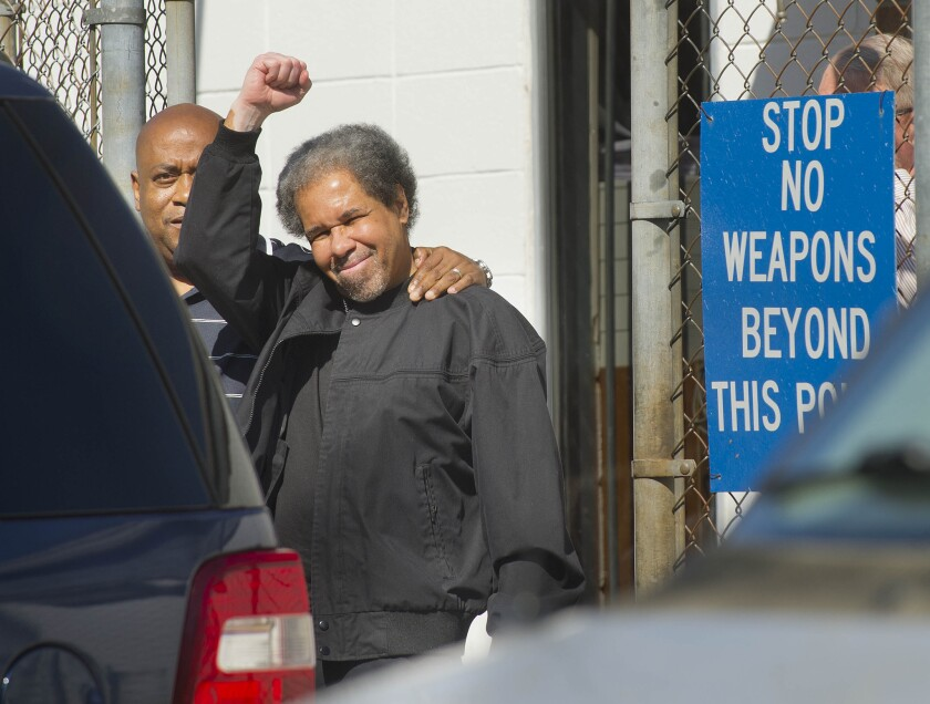 Albert Woodfox raises a clenched fist as he walks out of the West Feliciana Detention Center with his brother, Michael Mable, in St. Francisville, La.