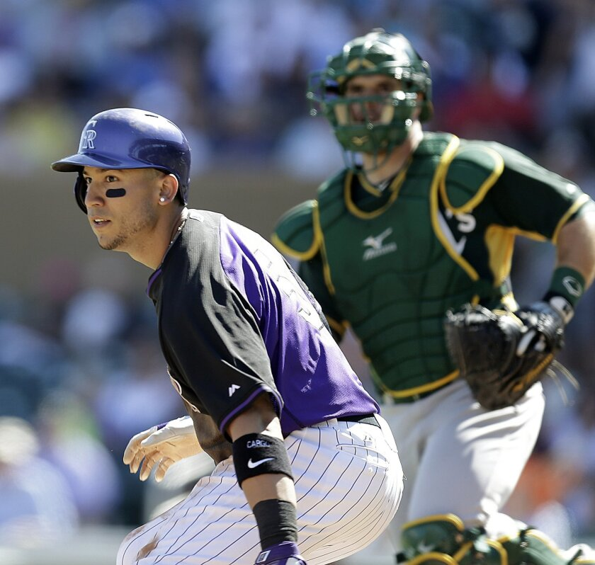 FILE - In this March 20, 2015 file photo, Colorado Rockies' Carlos Gonzalez, left, is caught in a rundown between third base and home plate in the third inning of a spring training exhibition baseball game against the Oakland Athletics, in Scottsdale, Ariz. (AP Photo/Ben Margot, File)