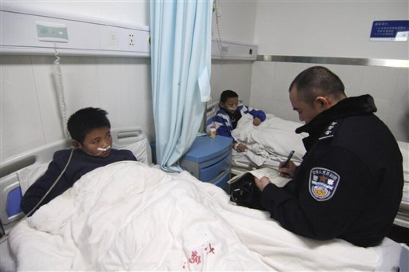 A policeman, right, takes notes while questioning an injured Yucai Middle School student in a hospital in Xiangxiang, in south China's Hunan province, Tuesday, Dec. 8, 2009. Eight youths were killed and 26 injured when students descending a crowded staircase after evening classes at the school in central China lost their footing amid a crush of bodies, state media and the local government reported Tuesday. (AP Photo)