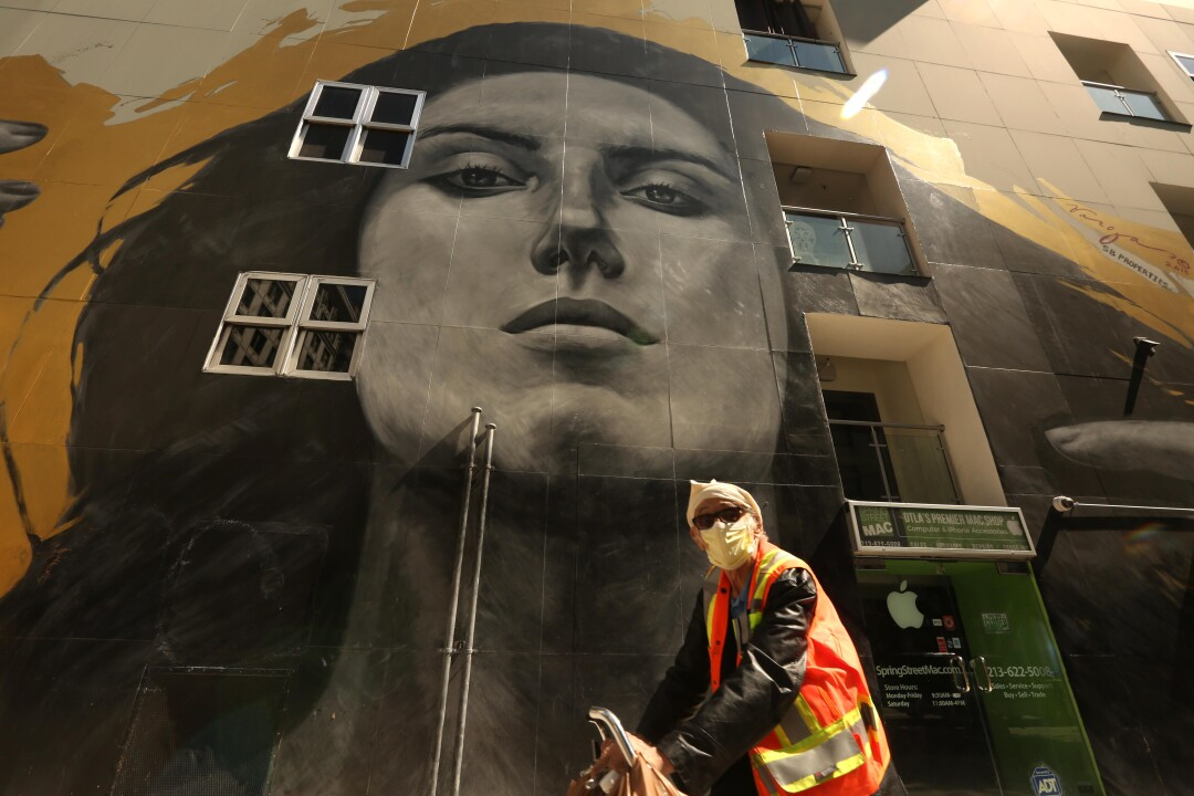 A bicyclist rides past a mural by street artist Robert Vargas in downtown Los Angeles.