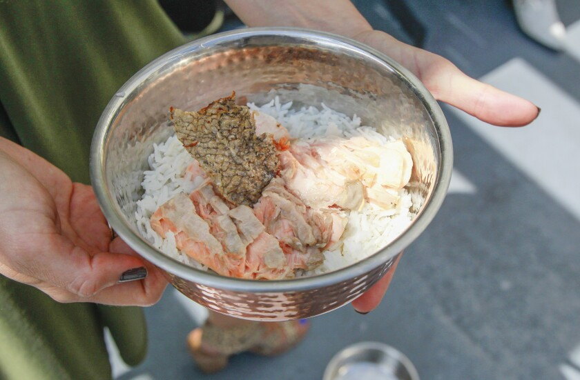 Grilled salmon with basmati rice, served in a hammered copper bowl, is one of the dishes on the dog menu at The Compass restaurant in Carlsbad Village.