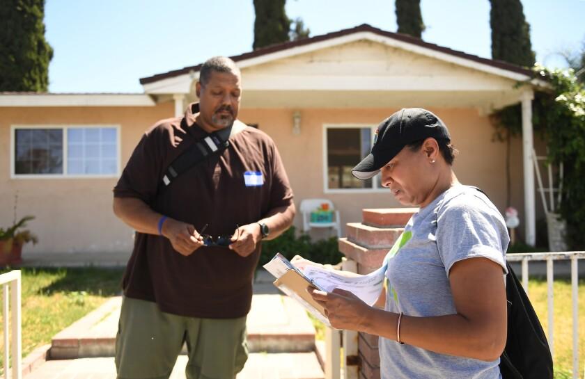 Democratic volunteers Derek Bryson and Pamela Sparrow, both from Los Angeles, knock on doors in a Si