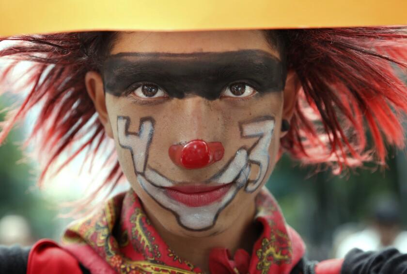 En esta imagen, tomada el 26 de septiembre de 2016, un manifestante disfrazado de payaso y con el número 43 pintado en la cara, posa para una fotografía durante una protesta en la Ciudad de México. La marcha se celebró en el segundo aniversario de la desaparición el 26 de septiembre de 2014 de 43 estudiantes de la normal rural de Ayotzinapa. La investigación inicial del gobierno señaló que los estudiantes fueron asesinados e incinerados. Pero expertos internacionales dudan sobre esta teoría y las familias tampoco la aceptan. (AP Foto/Marco Ugarte)