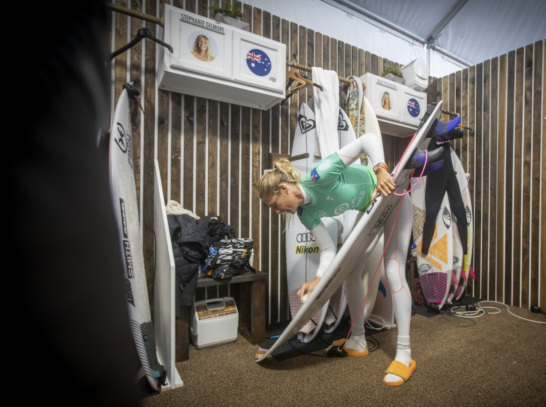 Seven-time WSL champion Stephanie Gilmore of Australia waxes up her board before her match with Johanne Defay