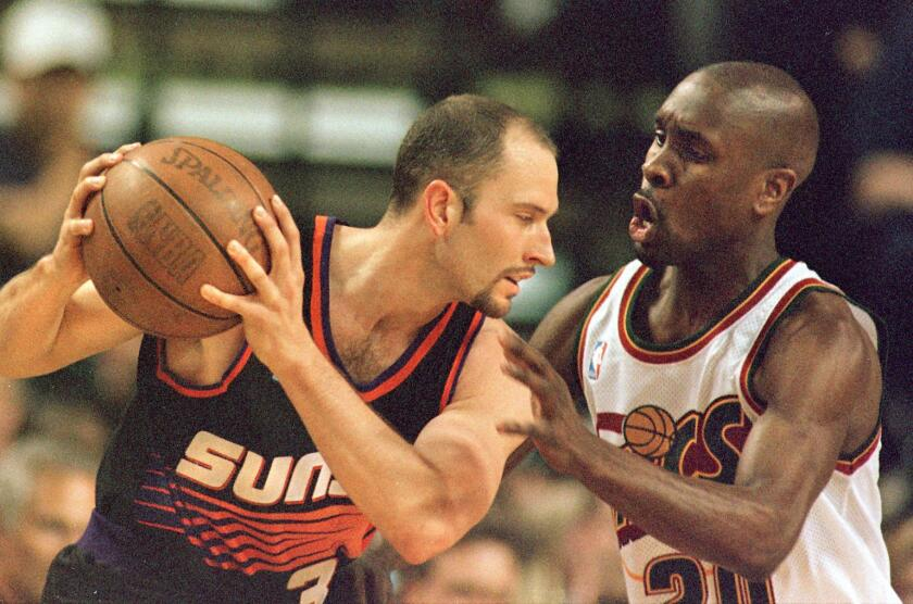 Phoenix Suns guard Rex Chapman, left, controls the ball in front of Seattle SuperSonics guard Gary Payton.
