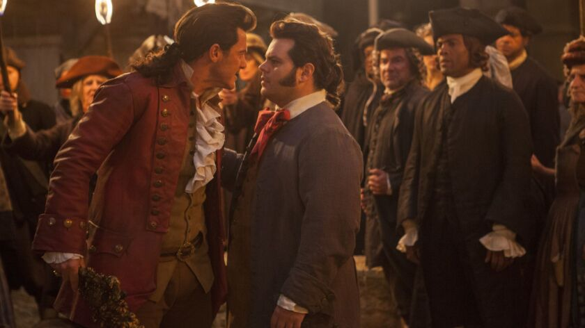 """This image released by Disney shows Luke Evans as Gaston, left, with Josh Gad as LeFou, in """"Beauty a"""