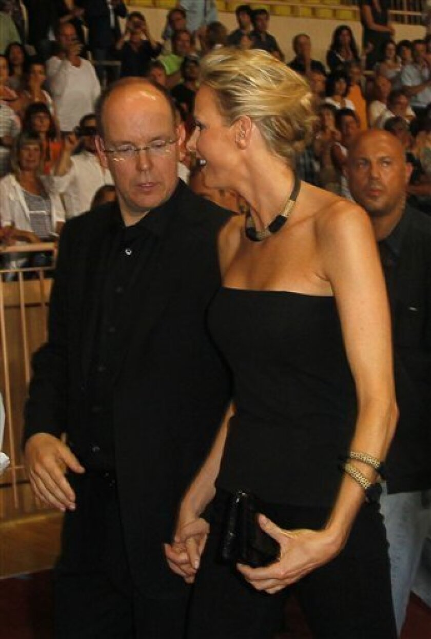 Prince Albert II of Monaco and his fiance Charlene Wittstock arrrive to a concert by US band The Eagles at the Stade Louis II, Thursday, June 30, 2011 in Monaco. The concert is part of the three day celebration that will include their wedding. (AP Photo/Francois Mori)