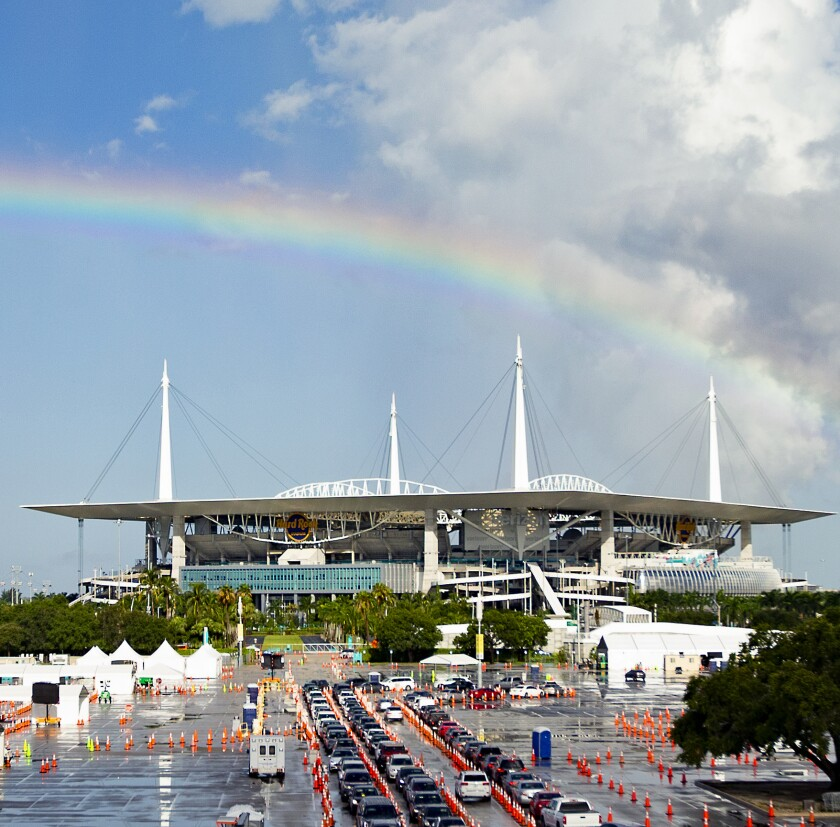 A view of a rainbow as vehicles line up at a COVID-19 drive-through testing center in Miami