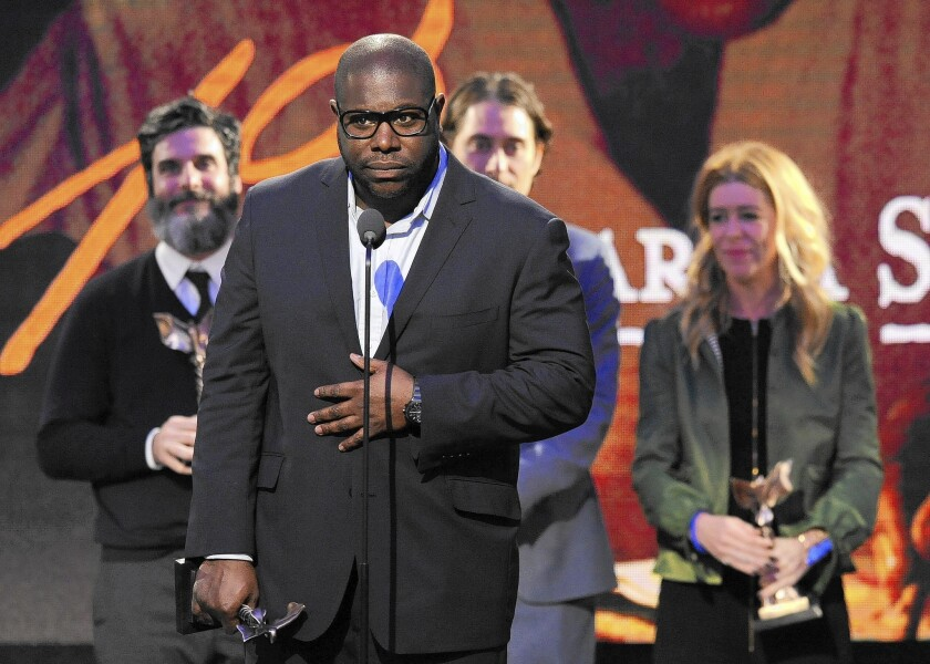 """Steve McQueen accepts the best feature award for """"12 Years a Slave"""" at the Film Independent Spirit Awards."""