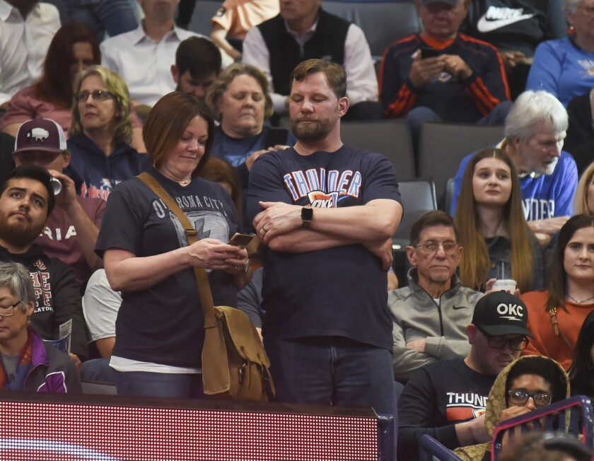 Basketball fans react after the announcement that a game between the Oklahoma City Thunder and the Utah Jazz on March 11 at Chesapeake Energy Arena has been postponed just before tip-off.