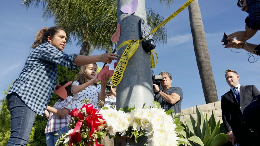 A woman and a young girl place notes on a pole across the street from the Chabad of Poway Synagogue after the shooting.
