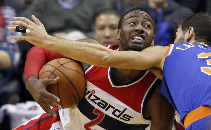 Washington Wizards guard John Wall (2) calls for a timeout after grabbing the ball in front of New York Knicks guard Jose Calderon (3), from Spain, in the first half of an NBA basketball game, Saturday, Oct. 31, 2015, in Washington. (AP Photo/Alex Brandon)