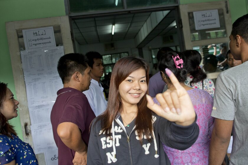 A voter shows her finger marked with ink, indicating she cast a ballot, at a polling station in Yangon, Myanmar.