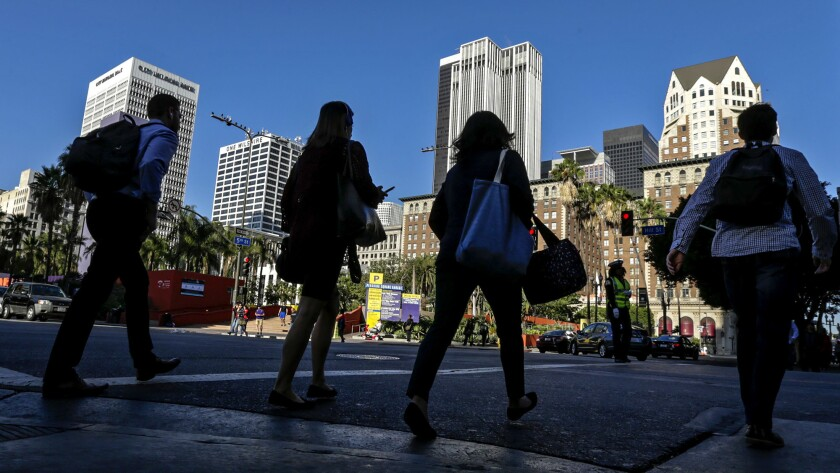 Pedestrians cross Hill Street across from Pershing Square in downtown L.A..