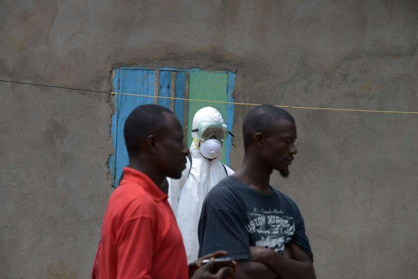 A medical worker with the Liberian Red Cross wears a protective suit while watching local residents in Banjol.