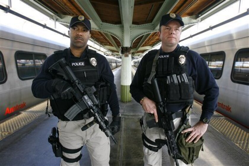 In this Feb. 15, 2008 file photo, Amtrak police officers Douglas Davison, left, and Keith Goerz, demonstrate the equipment they will carry as part of new security sweeps that will be effective this week at Union Station, in Washington.  On Thursday Jan. 8, 2009, Amtrak officials outlined their sec