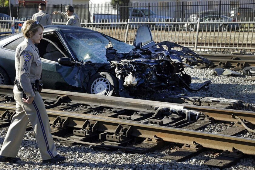 California Highway Patrol unidentified officers check the scene of a Metro Blue Line train derailed after colliding with a car and injuring one person in Los Angeles, on Monday, Nov. 23, 2015. County fire officials say one person was hospitalized in unknown condition. It wasn't immediately known if the injured person was in the car or train. Blue Line service has been suspended on that stretch of track and buses were sent to pick up passengers. Metro says delays are expected on northbound and southbound lines. (AP Photo/Nick Ut)