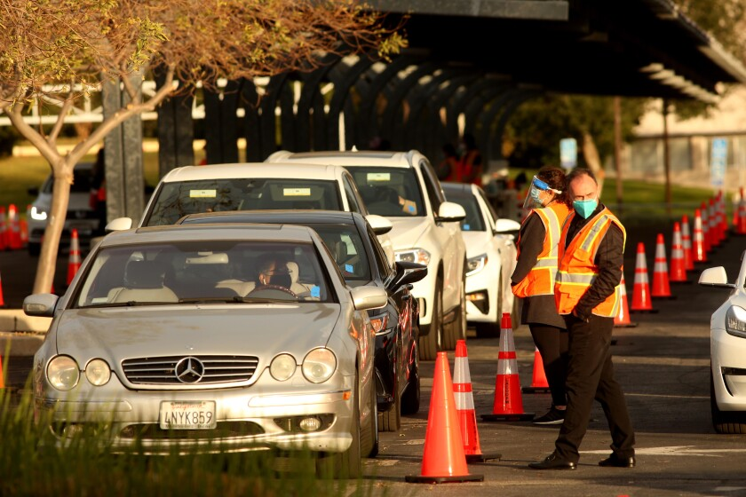 Motorists wait in their cars at a drive-through COVID-19 vaccination site at Cal State Northridge.
