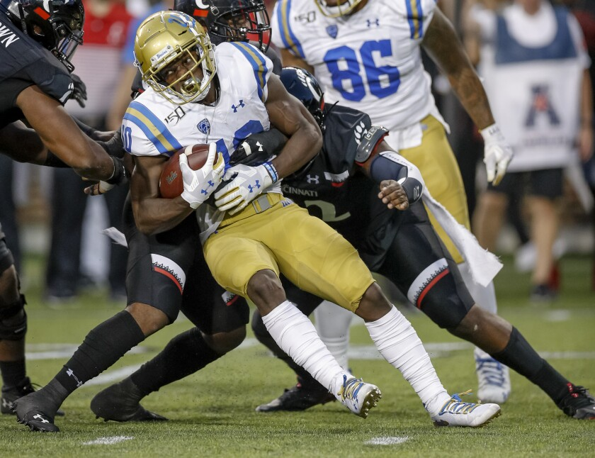 UCLA running back Demetric Felton tries to push for more yards during Thursday's loss to Cincinnati.