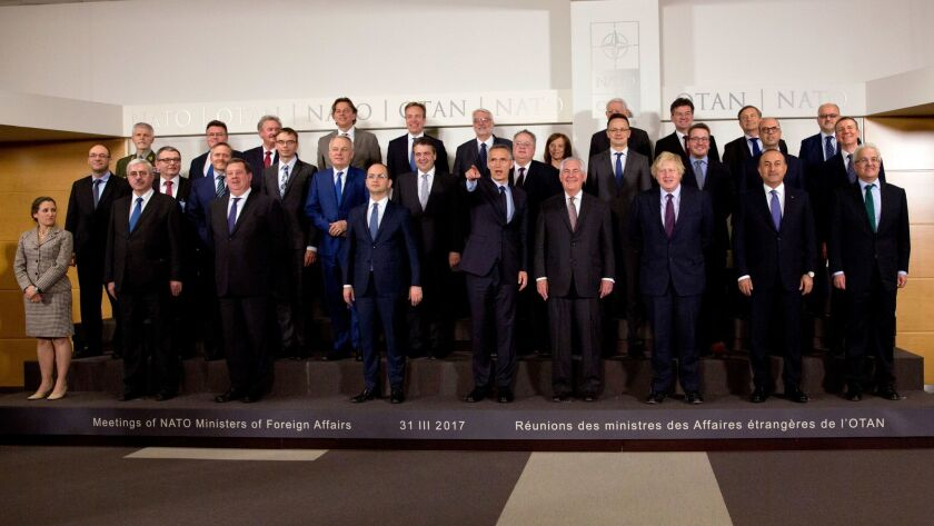 NATO Secretary General Jens Stoltenberg, center, points while standing next to U.S. Secretary of State Rex Tillerson during a group photo of NATO foreign ministers at NATO headquarters in Brussels on March 31.