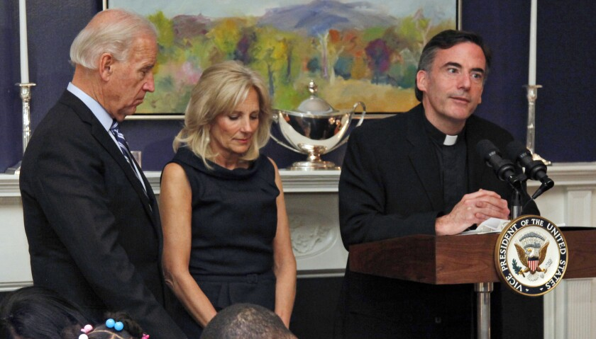 FILE - In this Nov. 22, 2010, file photo, Vice President Joe Biden, left, and his wife, Jill Biden, center, stand with heads bowed as the Rev. Kevin O'Brien says the blessing during a Thanksgiving meal for Wounded Warriors in Washington. Rev. O'Brien, a Jesuit priest who presided over an inaugural Mass for President Joe Biden, has resigned his position as president of Santa Clara University in Northern California, college officials said, after an investigation found he engaged in inappropriate, alcohol-fueled conversations with graduate students. Rev. O'Brien, at the direction of Jesuit officials, has begun a four- to six-month therapeutic outpatient program to address personal issues, including alcohol and stress counseling. (AP Photo/Carolyn Kaster, File)