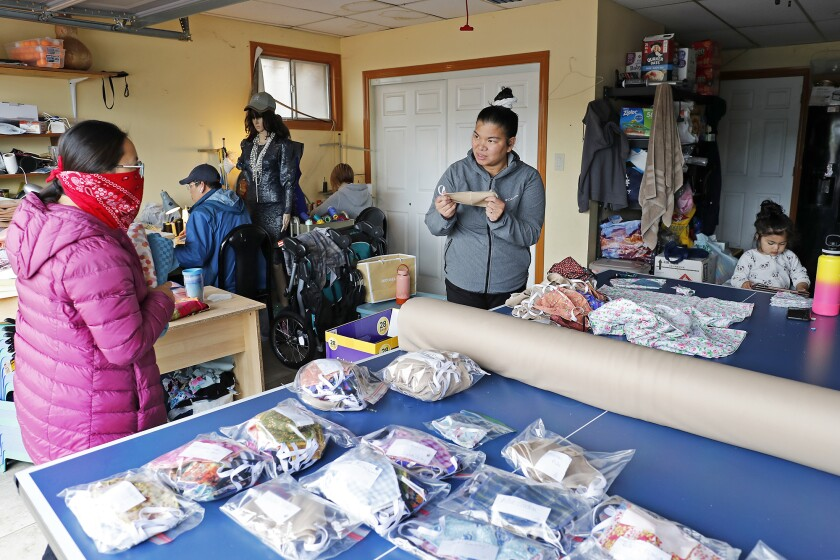 Trisha Garay, center, talks to Amy Guei, left, a speech therapist at Hoag Hospital, while she picks up face masks and donates some linen at Garay's home in Fountain Valley on Friday.