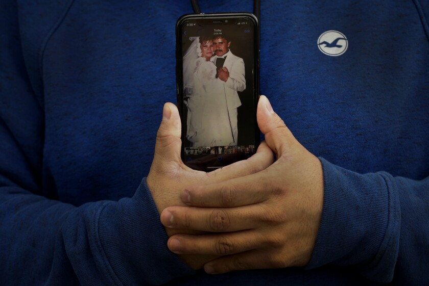 Omar Martinez holds a cellphone showing a photo of his parents' wedding.
