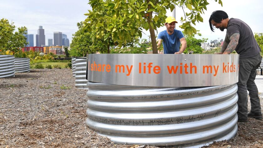 A piece of public art created by Fallen Fruit that incorporates quotes from members of the community is wrapped around the planters of the fruit trees by installers Winter Jenssen and Christian Lopez, right, at Los Angeles State Historic Park.