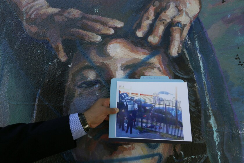 An attorney for Jesse Romero's mother holds a photo of Romero 14, after he was shot during a police chase in Boyle Heights.