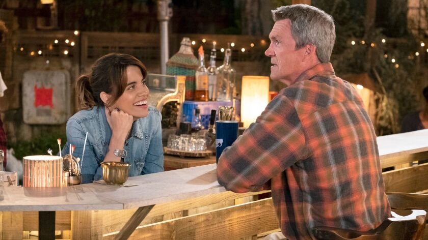 "Natalie Morales as Abby and Neil Flynn as Fred in the NBC sitcom ""Abby's,"" which is set at a backyard bar and was filmed outside in front of a studio audience."