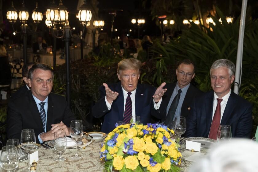 President Donald Trump speaks before a dinner with National Security Adviser Robert O'Brien, right, and Brazilian President Jair Bolsonaro, left, at Mar-a-Lago, Saturday, March 7, 2020, in Palm Beach, Fla. (AP Photo/Alex Brandon)