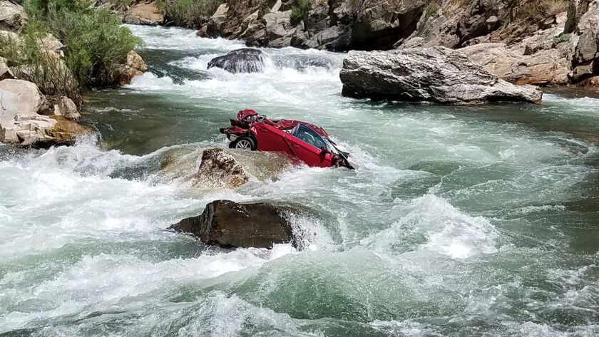 This Aug. 5, 2017, photo provided by the Fresno County Sheriff's office shows a car in the middle of the Kings River near Fresno. Efforts to remove the car and retrieve the bodies have been hampered by rugged terrain.