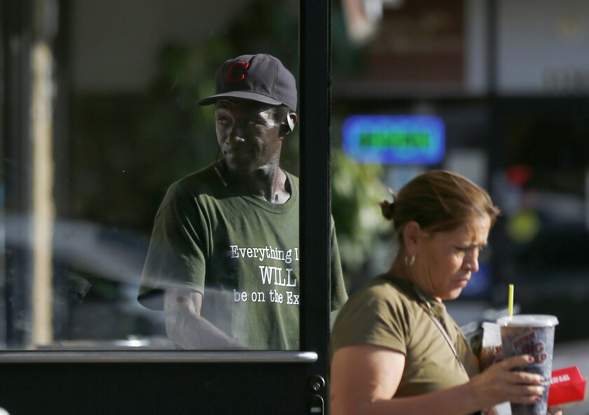 Majesty, a homeless man, holds the door for a customer of a 7-Eleven store along Riverside Drive in North Hollywood.
