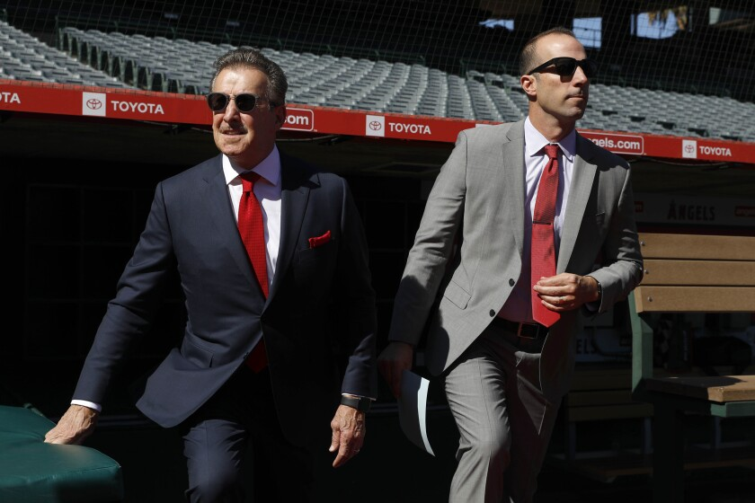 Angels owner Arte Moreno, left, and general manager Billy Eppler make their way onto the field at Angel Stadium to introduce Joe Madden as the team's new manager Thursday.