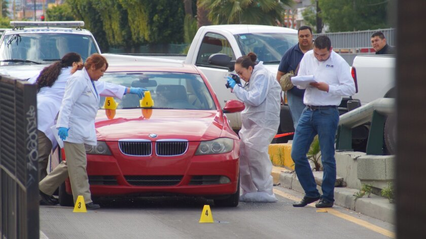 Investigators at a crime scene last week in Tijuana following the shooting of a state agent.