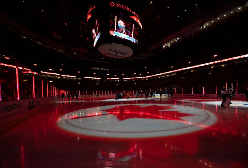 A maple leaf is projected on the ice during the singing of the Canadian national anthem at Rogers Arena in Vancouver.