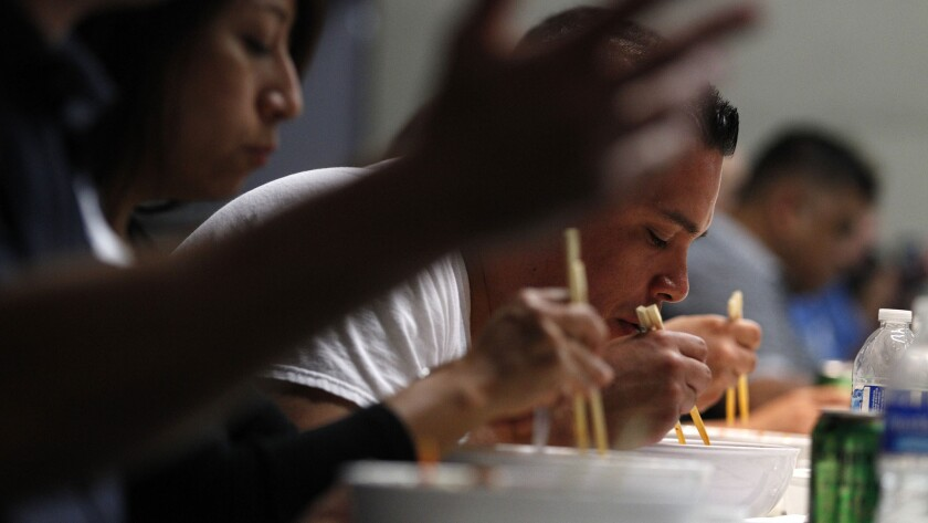 Tony Garcia, center, an officer with the Los Angeles Police Department's Olympic Division, uses chopsticks to eat bibimbap during a Korean cultural workshop for law enforcement.