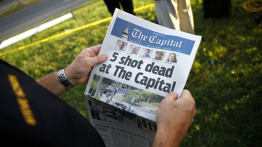 Steve Schuh, county executive of Anne Arundel County, holds a copy of Friday's edition of the Capital near the scene of a shooting at the newspaper's office.