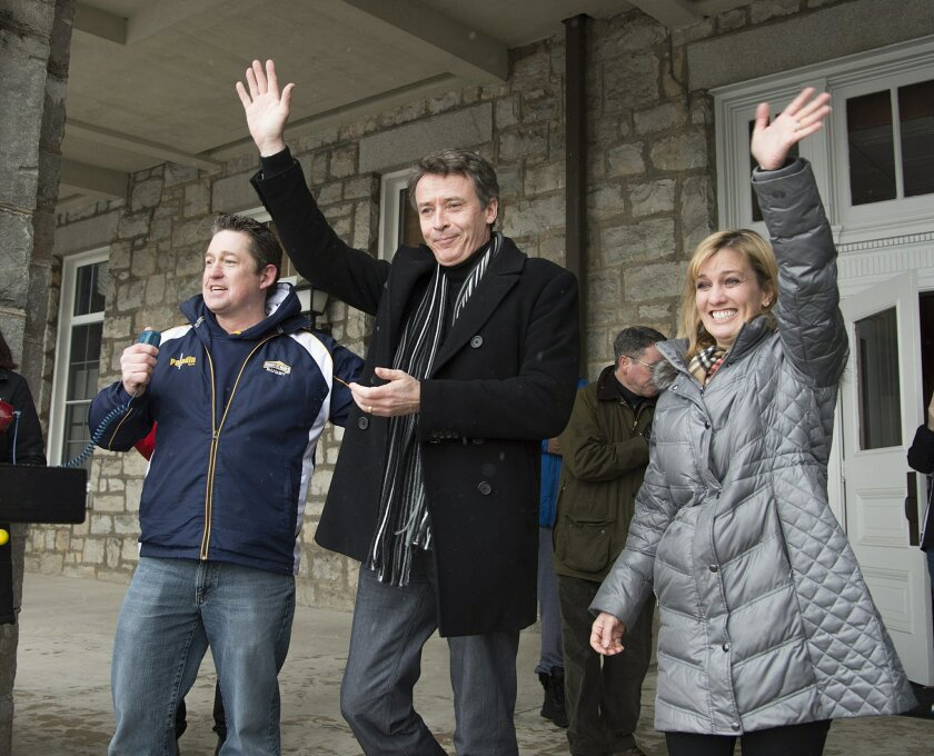FILE- In this Monday, Feb. 15, 2016, file photo, Mount St. Mary's President Simon Newman, center, prepares to address a rally of students with his wife, Michelle, at his side, in Emmitsburg, Md. At left is rugby coach Jay Myles. A plan to identify freshmen most likely to fail has erupted into a sca