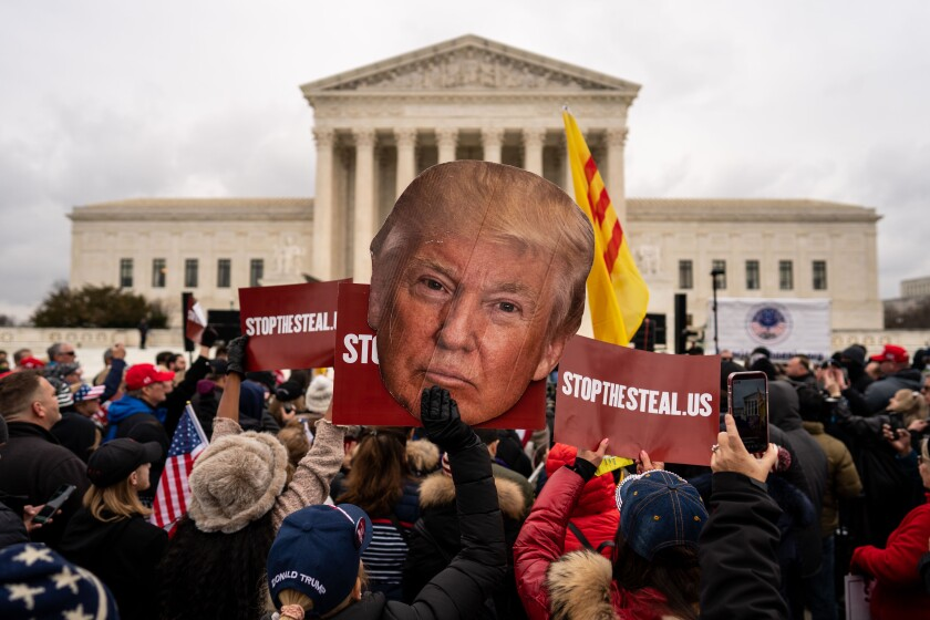 "People listen to speakers during a ""Stop the Steal"" rally in front of the Supreme Court"