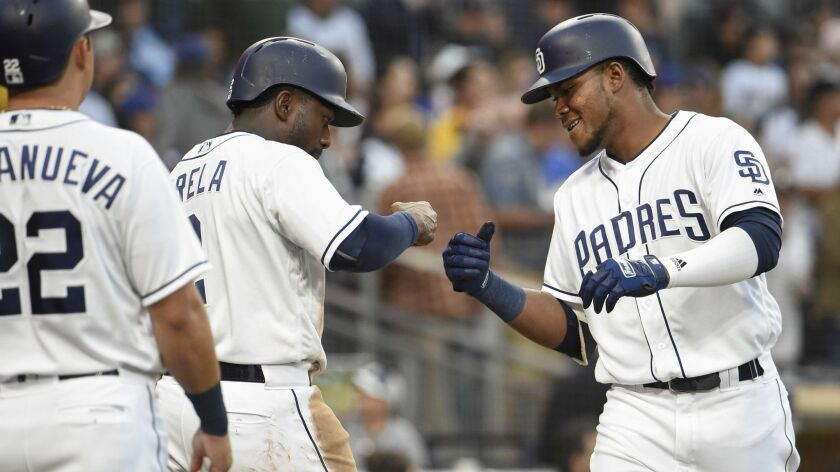 The Padres' Franchy Cordero, right, is congratulated by Jose Pirela as Christian Villanueva looks on after Cordero hit a three-run home run during the fourth inning of a baseball game against the New York Mets at Petco Park on April 28, 2018 in San Diego, California.