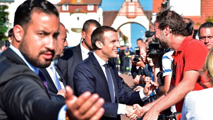 French President Emmanuel Macron (C) shakes hands with people after he voting in Le Touquet, norther