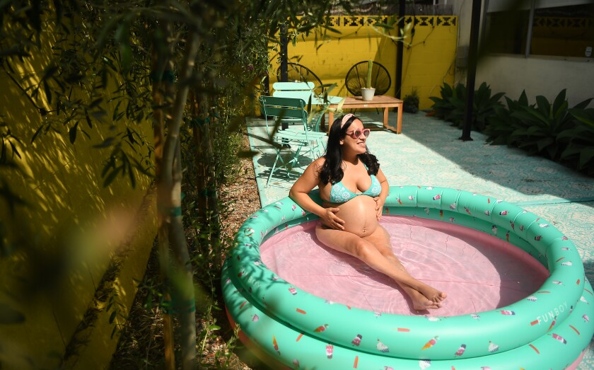 Sofia Gonzalez, nine months pregnant, finds a little relief from the heat in a backyard kiddie pool.