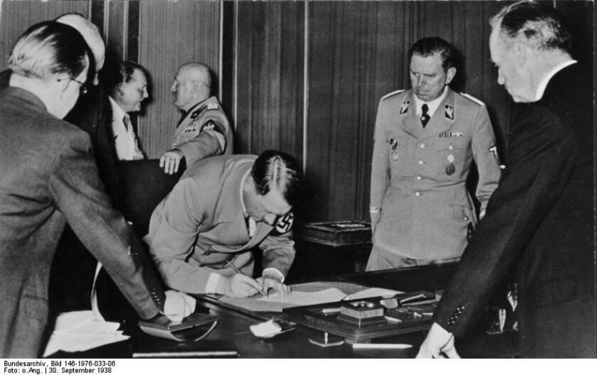 Adolf Hitler  at the signing of the Munich Agreement in 1938 with Benito Mussolini and Herman Göring in the background,  Julius Schaub on Hitler's left and Joachim von Ribbentrop to the right, partly from behind. From the German Federal Archives on Wikimedia Commons - http://commons.wikimedia.org/w