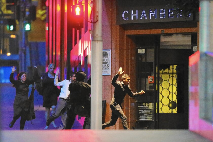 People run from the Lindt Chocolat Cafe in Sydney, Australia. Police said they stormed the cafe after hearing gunshots from inside.