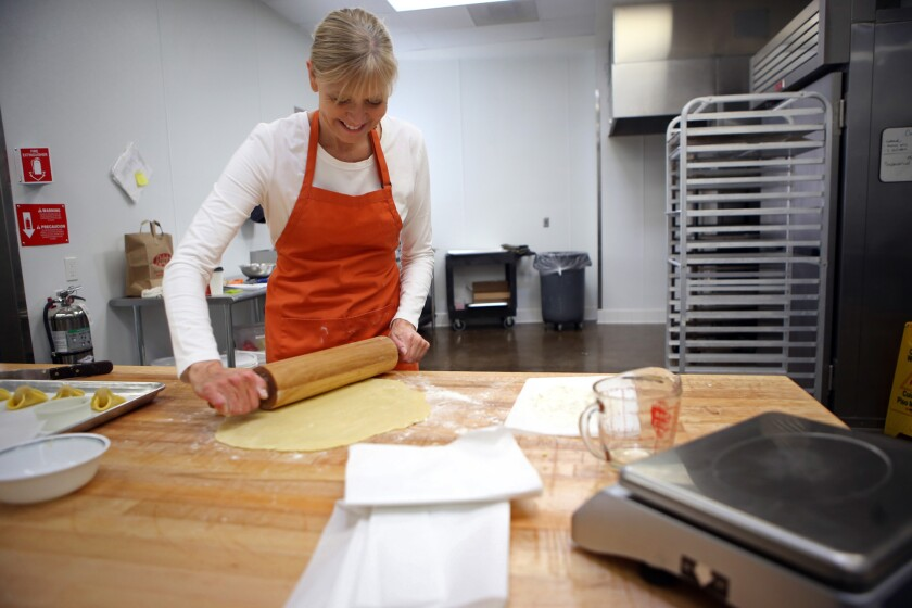 Baker Karen Hansen, owner of Copenhagen Pastry, rolls out the dough to make Napoleon hat cookies at her bakery in Pasadena on Dec. 7.