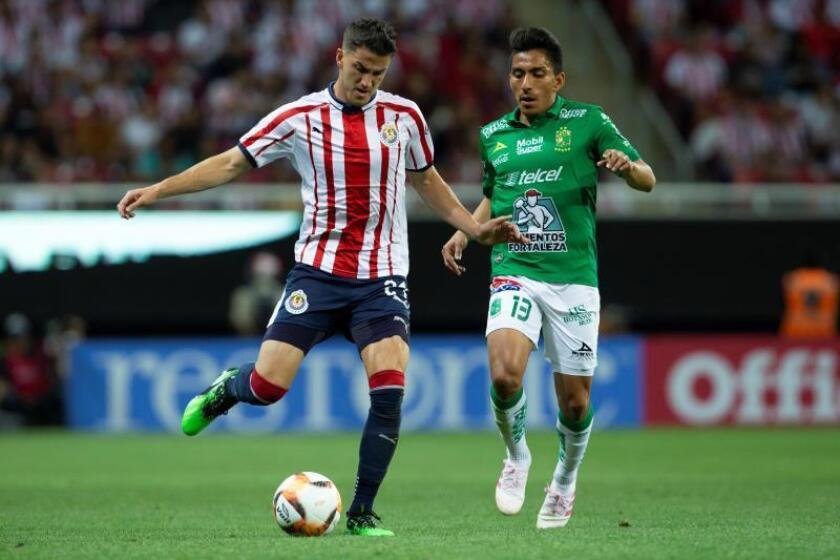 El jugador de Chivas Hiram Mier (i) disputa el balón con Ángel Mena (d) de León durante el juego correspondiente a la jornada 16 del torneo mexicano de fútbol, celebrado en el estadio Akron, en la ciudad de Guadalajara (México). EFE