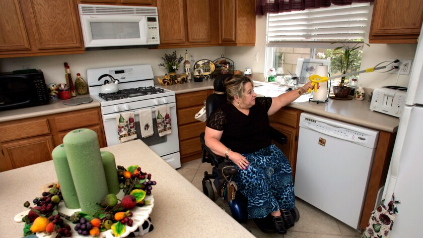 A woman demonstrates for a photographer in 2006 how—despite having the space between her counters widened to accommodate a wheelchair—electrical switches remain out of reach and counters are too high for her to reach many objects.