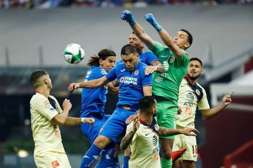 El arquero de América Agustín Marchesin (d) despeja un balón ante Cruz Azul este jueves, durante el partido de ida de cuartos de final del Torneo Clausura 2019 realizado en el Estadio Azteca en Ciudad de México. EFE/Archivo